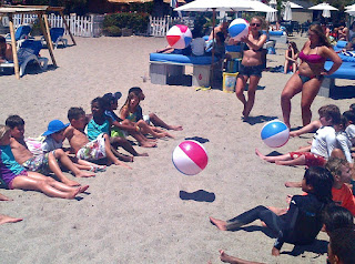 Keiki campers and their camp counselors sitting on the beach playing with beachballs at Aloha Beach Camp at Paradise Cove