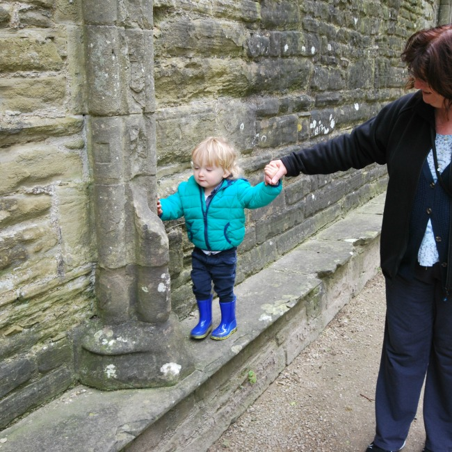 toddler walking on wall hold adults hand