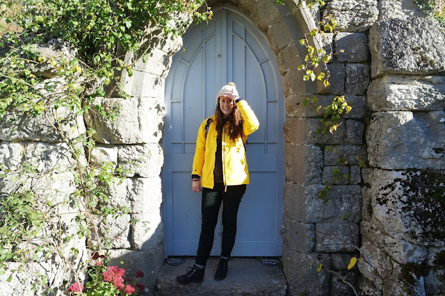 I'm wearing a yellow coat and standing in front of a small blue door set in an old stone wall