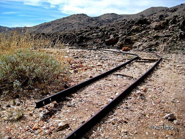 Contact Mine's old ore cart rails probably led to the tailing piles found below the shafts.