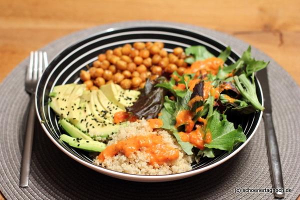 Buddha Bowl mit gerösteten Kichererbsen, Quinoa, Wildkräutersalat, Avocado und einem Dressing aus gegrillter Paprika