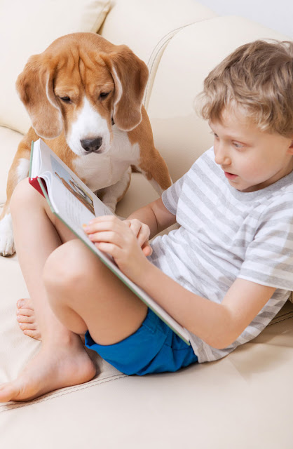 A boy reads to his pet dog at home