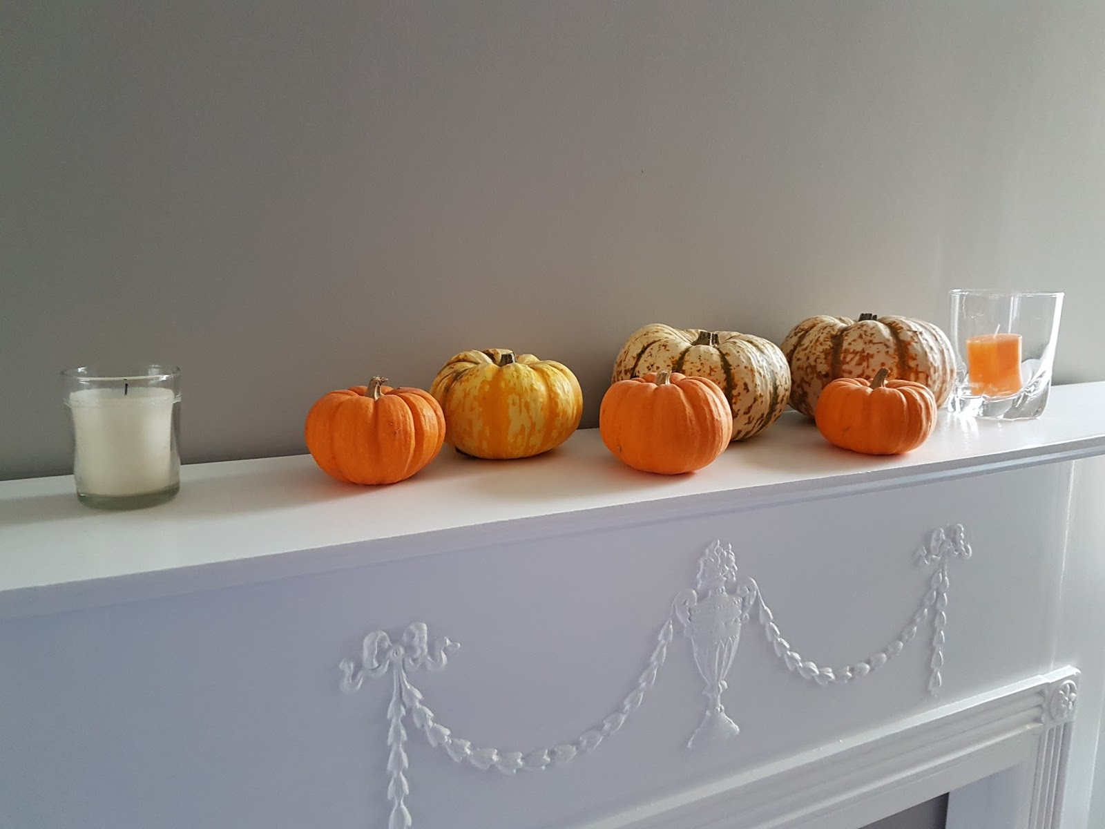 several munchkin pumpkins and candles on a mantelpiece
