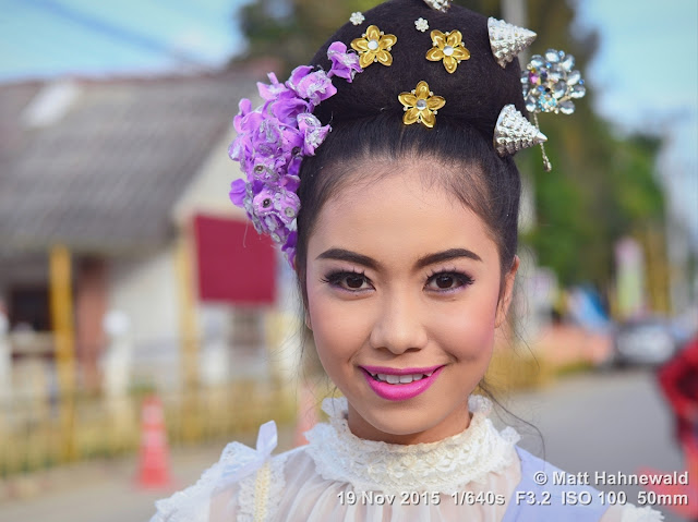 Matt Hahnewald; Facing the World; Asia; Northern Thailand; Mae Chaem; people; closeup; portrait; street portrait; headshot; smiling; Thai girl; Thai smile; Land of Smiles; world cultures; travel; eye contact; Nikon DSLR D3100; 50 mm prime lens; colour; face; outdoor; street parade; make-up; beautiful; folk costume; Lanna tradition; dressed up to the nines; floral hair wreath; lip make-up