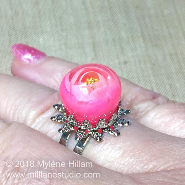 UV Resin Rose bead set in a silver filigree ring base.