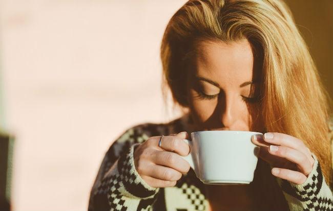 Donna che beve caffè: può ostacolare la gravidanza