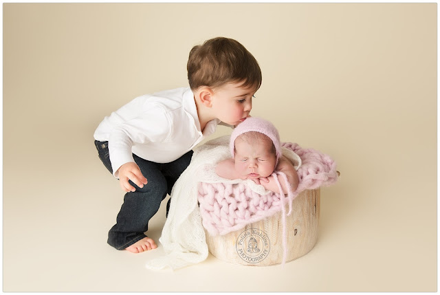 Big (3year old) brother is kissing his newborn sister. Newborn sister is in the bucket, brother is touching her forehead with his lips.
