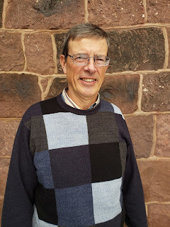 Man wearing glasses and sweater with blocks of gray, white and black stands in front of a stone wall