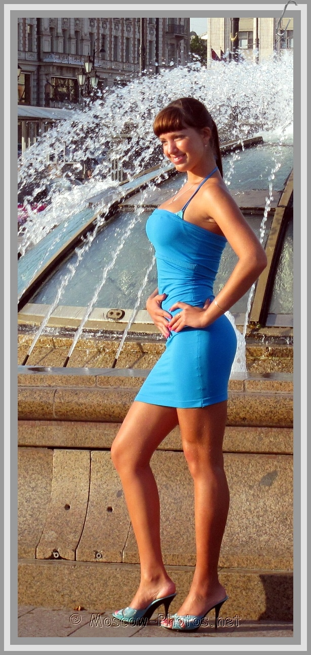 Slim russian girl in mini-dress posing next to the fountain