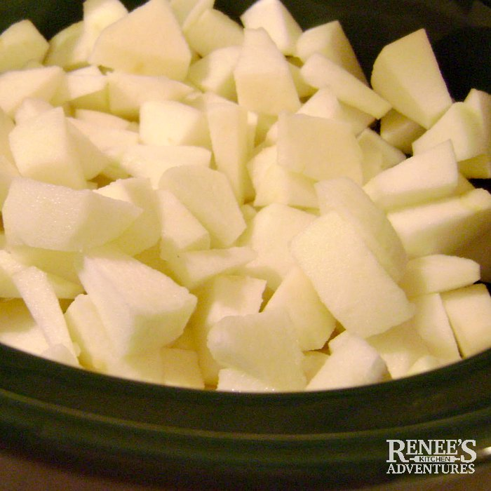 Apples cut up and ready to cook in slow cooker for slow cooker applesauce