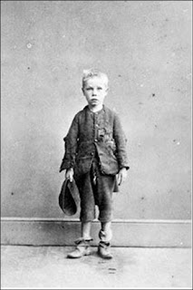 A booted ragged child, probably a Victorian or Edwardian photograph