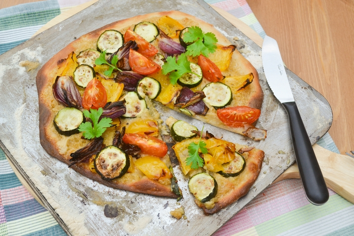 A homemade white pizza with a hummus sauce, roast vegetables, herbs and spices.