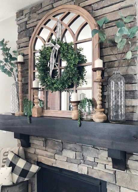 Summer farmhouse styled fireplace, arched mirror, wood candle sticks, glass vases with faux greenery, boxwood wreath