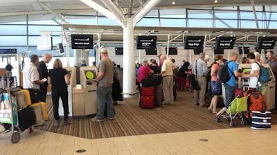 Photo of passengers using self-service kiosks at Brisbane Airport