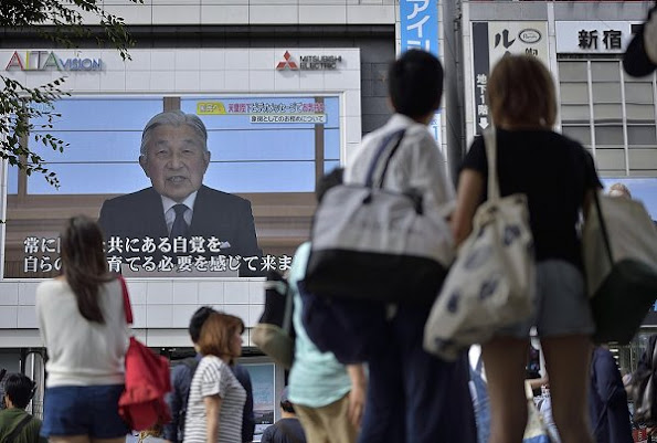 Pedestrians watch a large screen broadcasting Japanese Emperor Akihito's video message on his thoughts in Tokyo. Crown Prince Naruhito and Crown Princess Masako