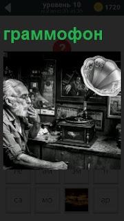 Мужчина с бородой и сигаретой слушает старинный граммофон на столе  с задумчивым видом на лице