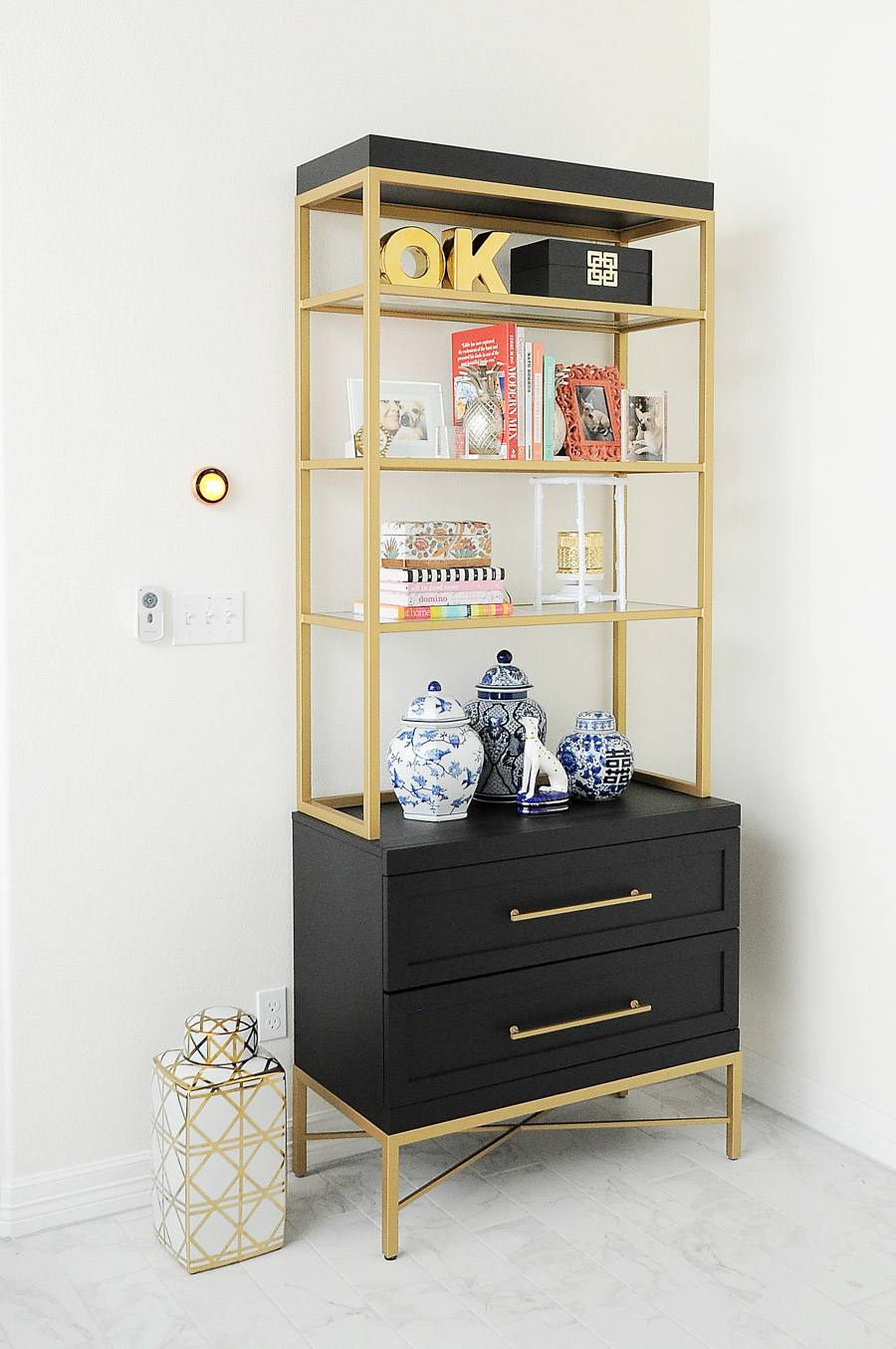 A gorgeous black and gold etagere styled with ginger jars, thrifted finds, chinoiserie decor and design books. Love the curated and chic look!