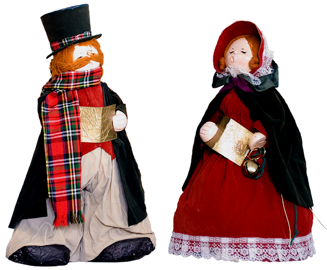 Two vintage papier mache carolers dressed in velvet, he's wearing a tophat and plat scarf, she's wearing a red-velvet dress, green cape and red bonnet.