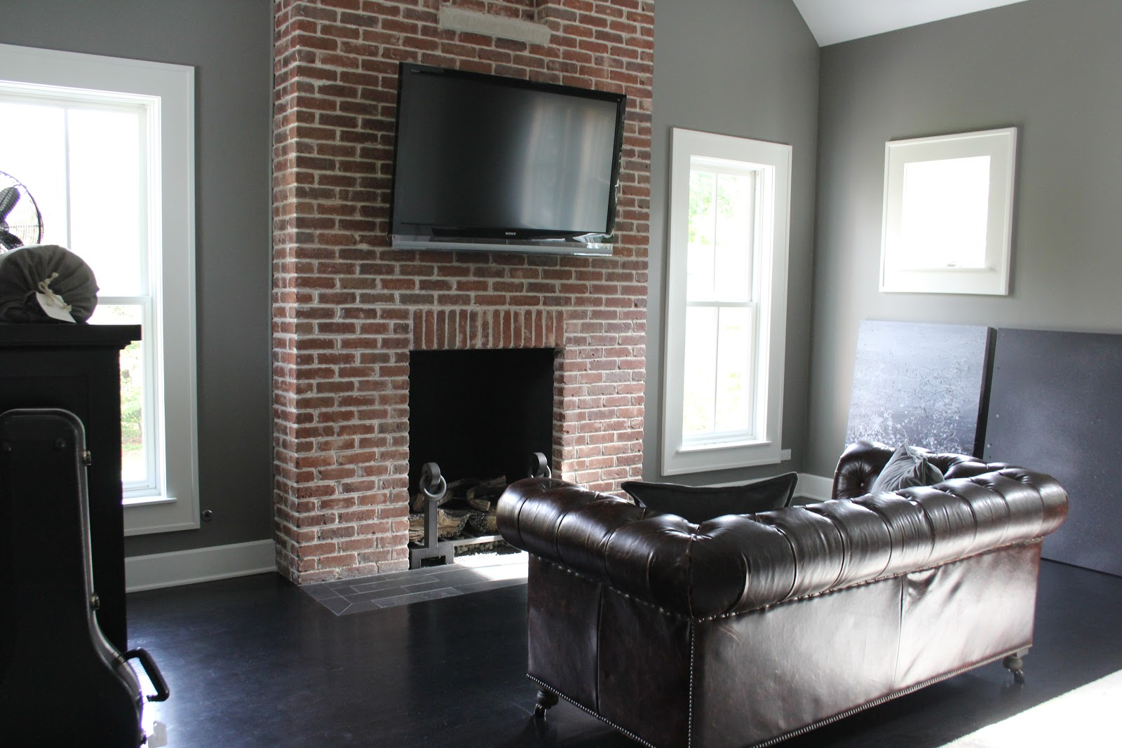 Exposed brick fireplace in modern farmhouse master bedroom on Hello Lovely Studio