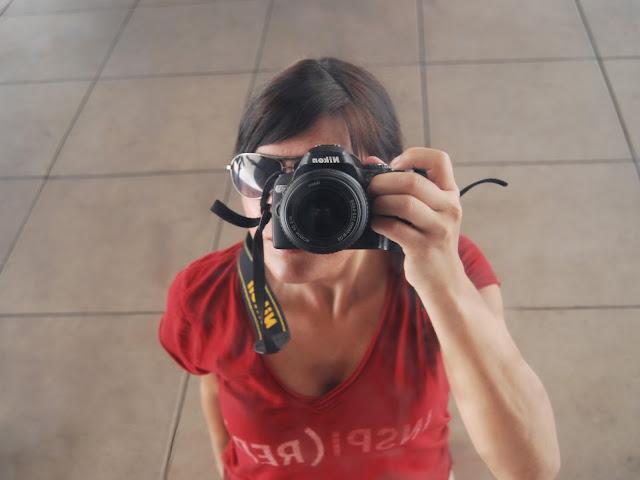 Autorretrato (reflejo) de una chica con cámara y camiseta roja