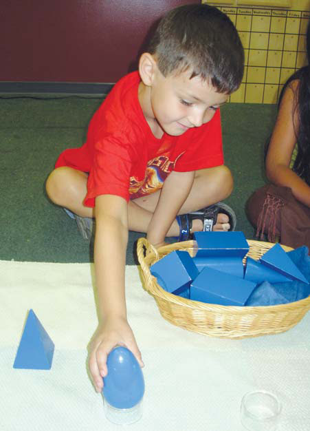 NAMC when is it too late for my child to attend a montessori school child working with geometric solids