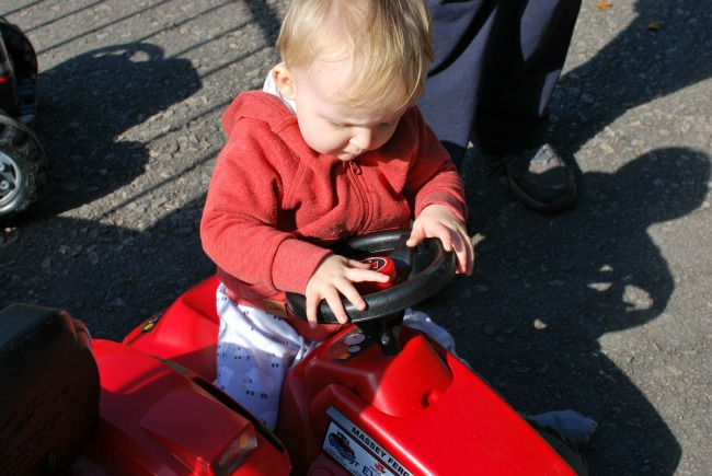 child examining button on tractors steering wheel