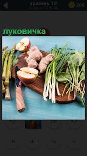 на разделочной доске лежат имбирь, нож, луковичка для приготовления