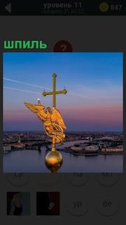 Высоко над городом стоит шпиль с крестом и металлическим шаром