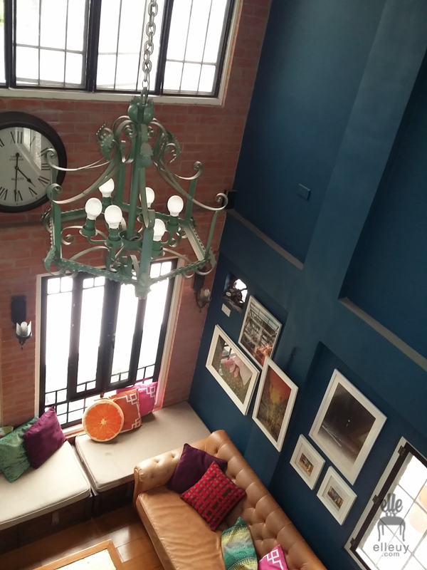 Brick walls, loft living room, high ceiling, wall of windows, vintage living room, navy blue walls, wrought iron chandelier