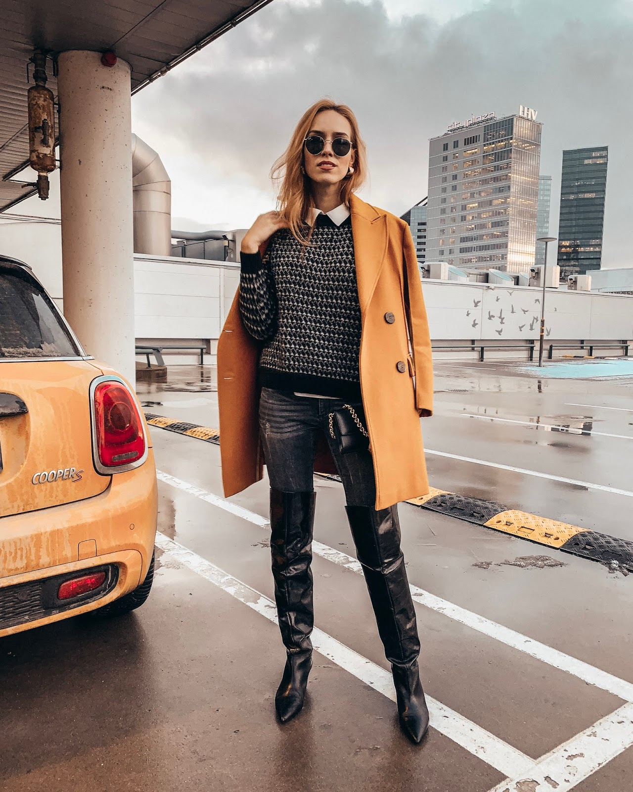 yellow coat black jumper jeans over knee boots winter style