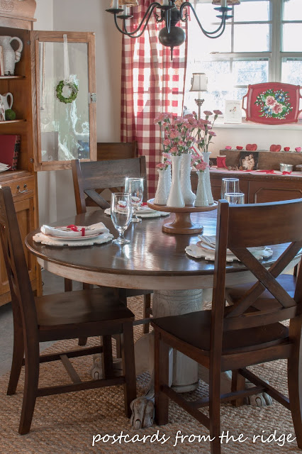 French farmhouse style dining area with buffalo check curtains, milk glass, ironstone, and more.