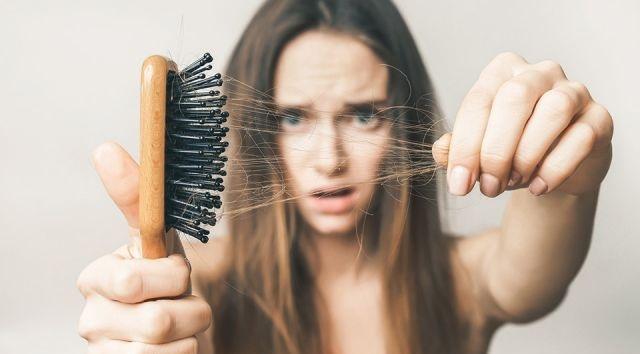 vajzë duke parë krëhërin se si i kanë rënë flokët