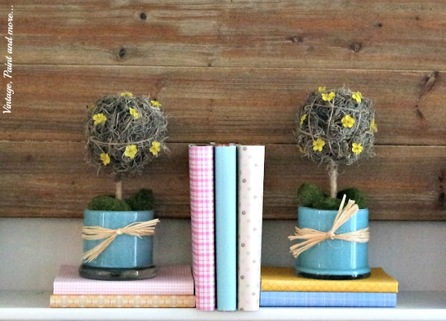 paper covered books with diy topiaries on a pastel mantel