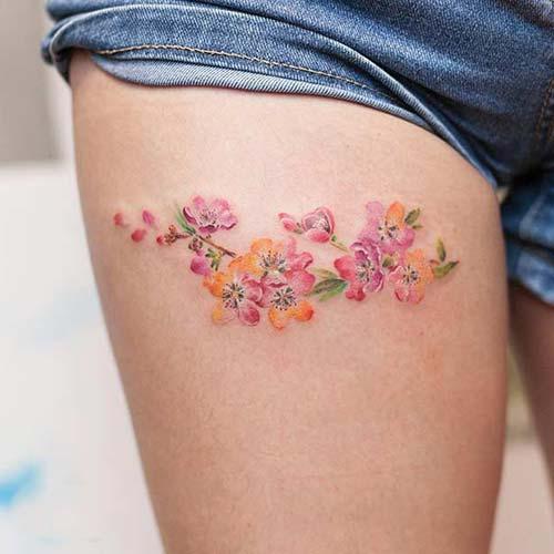 kadın üst bacak renkli çiçek dövmesi woman thigh colorful flowers tattoo