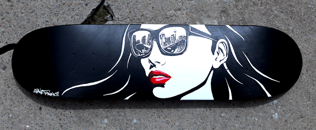 Picture of a custom commission painted skateboard with a comic noir black and white pop art style woman's portrait with red lipstick wearing sunglasses with the reflection of Calgary Alberta Canada in the lenses.