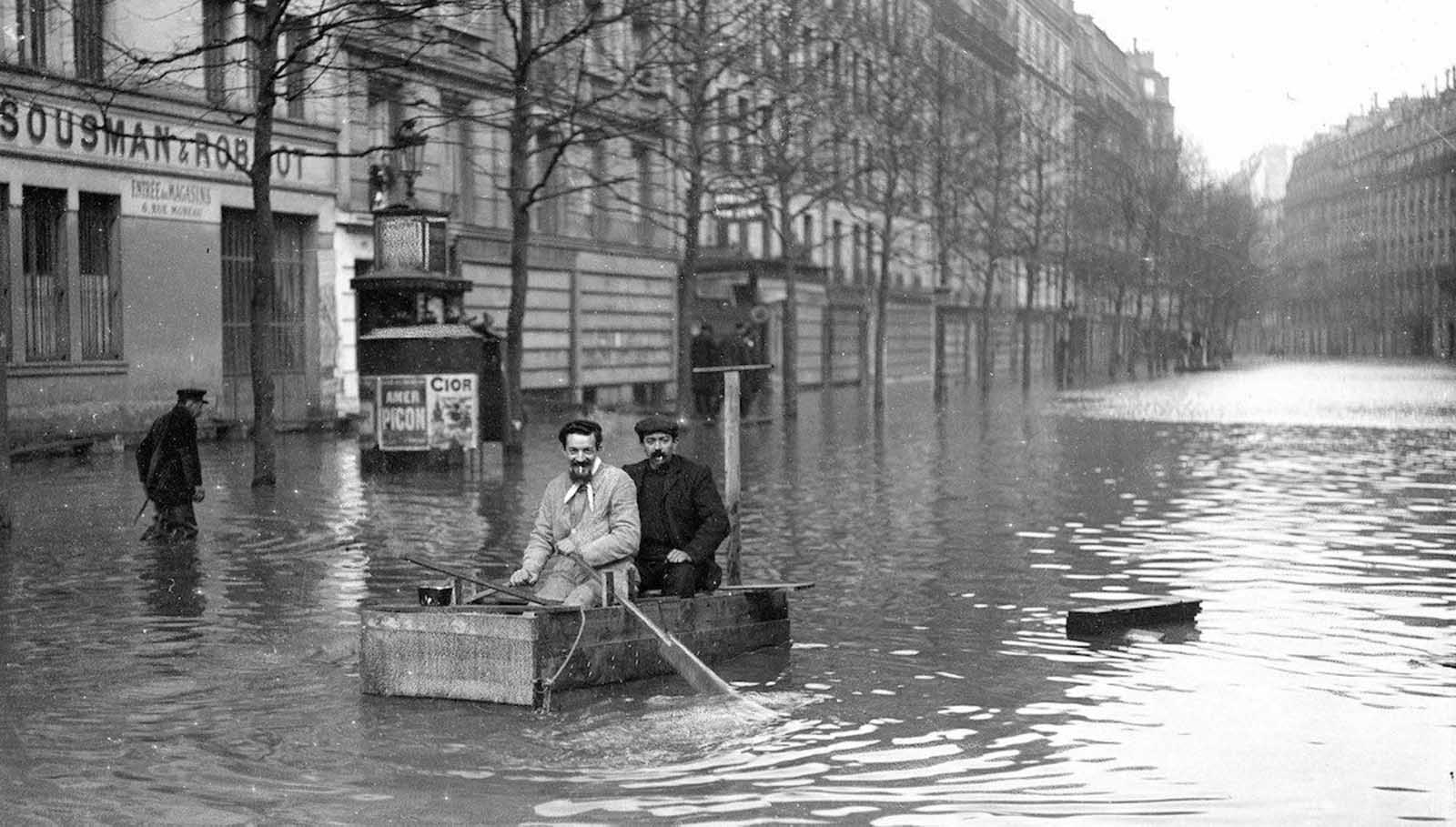 Two men travel down the street in an improvised boat.