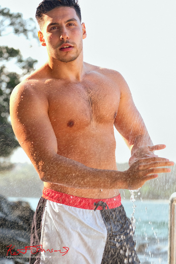 Outdoor harbour beach location with shower spray. Male modelling portfolio shot on Location in Sydney Australia by Kent Johnson.
