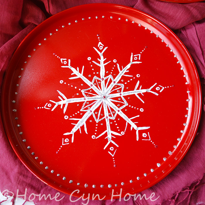 This snowflake plate started as a stainless steel plate that got spray painted first and then decorated with acrylic paint and glitter glue