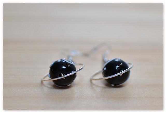 boucles d'oreilles argentées et perles noire vues de dessous