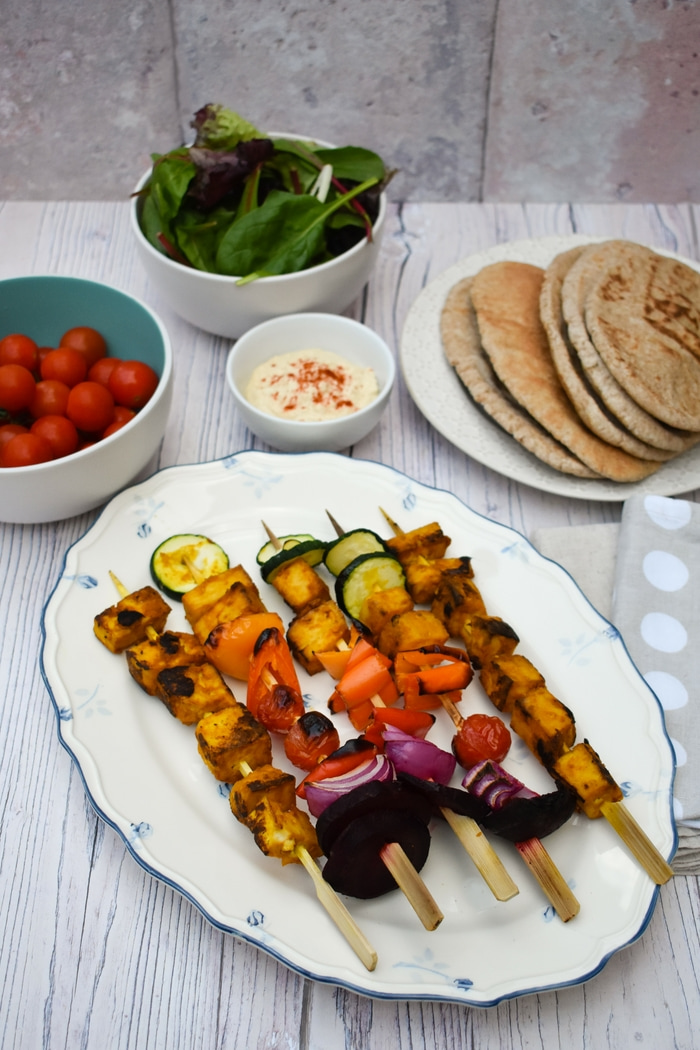 Grilled Tandoori Tofu Skewers served with wholemeal pitta bread, salad leaves, cherry tomatoes and hummus