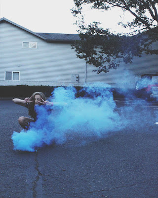 chica adolescente sentada con humo azul