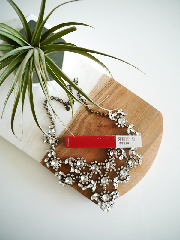 Flat lay featuring Maybelline Super Stay Matte Ink lipstick in classic red 'Pioneer', a sparkly statement necklace from J. Crew, and an air plant in a white geometric bowl