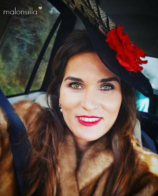 Primer plano de Leticia de boda con abrigo de piel y tocado negro y rojo con plumas by malonsilla con pelo suelto