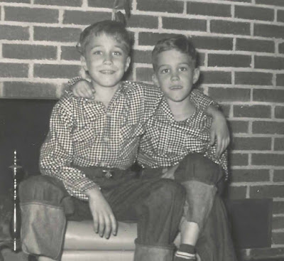Two boys in front of fireplace during Christmas in the 1950s