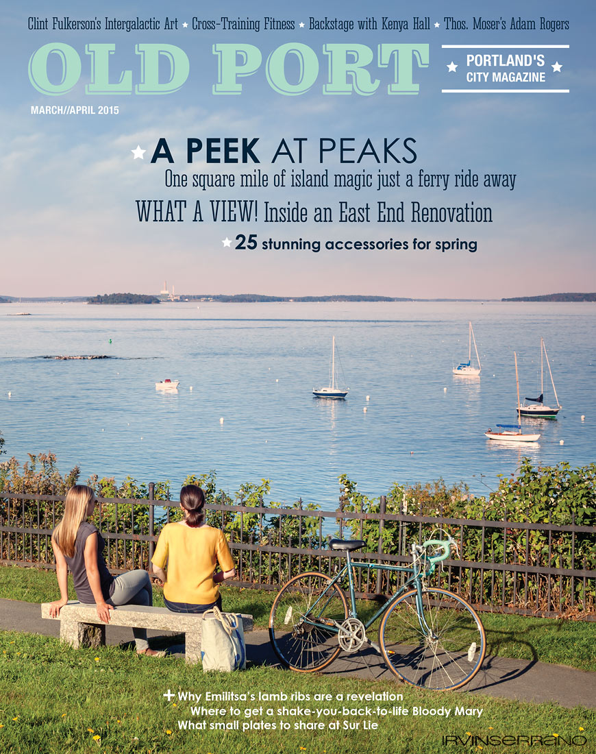 Two women sit on a bench in early spring overlooking Casco Bay and the docked sailboats outside of Portland, Maine.