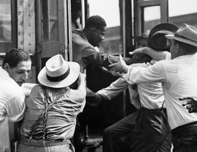 A man is dragged from a street car on June 21, 1943, during fighting near Detroit's downtown section.