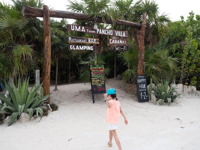 Niña enfrente de la entrada a un restaurante en la arena, rodeada de palmeras