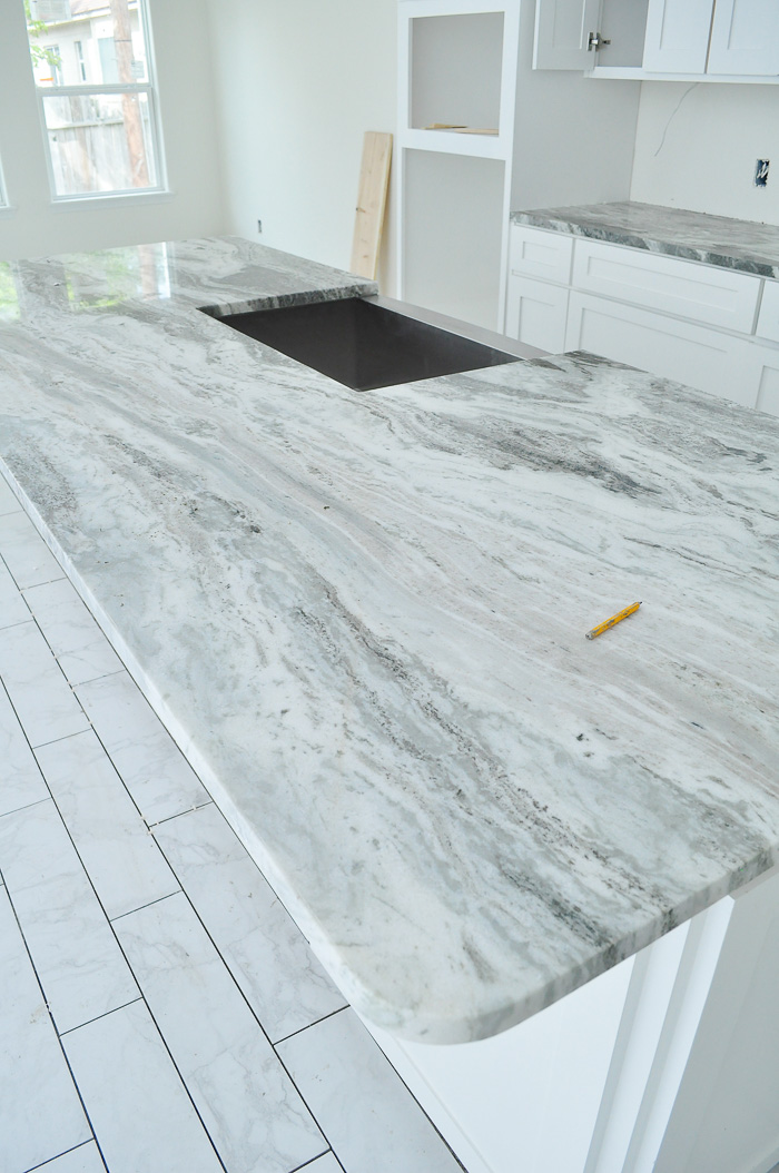 Marble look tile flooring in a white kitchen with shaker cabinets and fantasy brown granite. | via monicawantsit.com