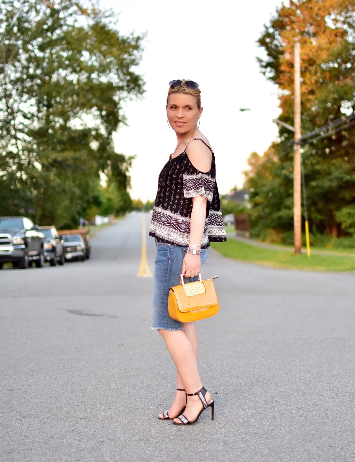 Monika Faulkner styles a cold-shoulder boho blouse, denim boyfriend shorts, ankle-strap sandals, and yellow patent mini-bag