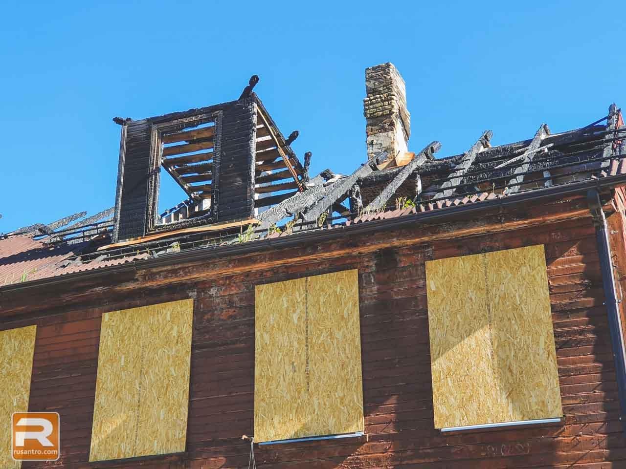 Koka ēka ar ugunsgrēkā nopostītu jumtu un aizsistiem logiem